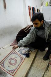 Repairing miniature carpets in Qom
